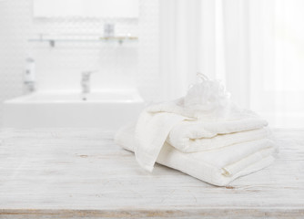 Fluffy towels and wisp of bast over blurred bathroom background