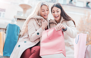Shopping time. Beautiful women take a break near the fountain after shopping. Consumerism, shopping, lifestyle concept