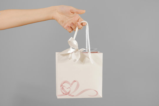 Blank white paper gift bag with hearts mock up holding in hand. Empty plastic package mockup hold in hands isolated. Consumer pack ready for logo design or identity presentation. Product packet handle