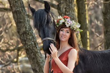 Brunette woman in a red dress with a wreath of flowers on her head and a black horse.