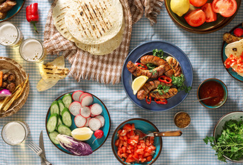 Dinner party table with grilled sausage, beer and different dishes