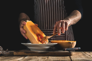 Male chef preparing healthy food from pumpkin on wooden table