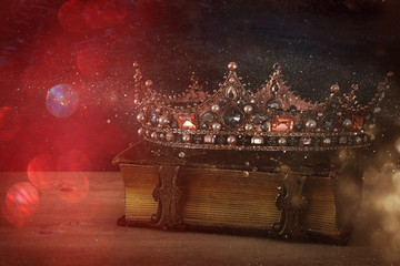 low key image of beautiful queen/king crown on old book