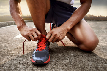 Man tying running shoes