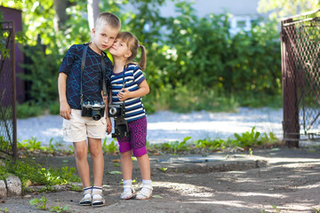 Little boy and a little girl wit two vintage cameras standing to