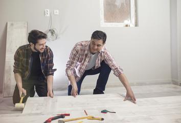 Carpenter installing a new laminated wooden flooring