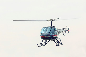 Black helicopter flying in front. Light multipurpose helicopter five-seat all-metal construction.