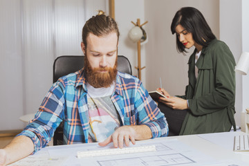 Man working with blueprint while woman writing