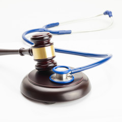 Close up shot of a judge gavel and a stethoscope