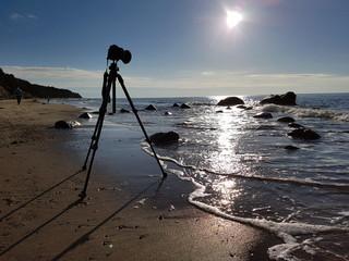 Fotoapparat auf Stativ fotografiert Sonnenuntergang am Meer
