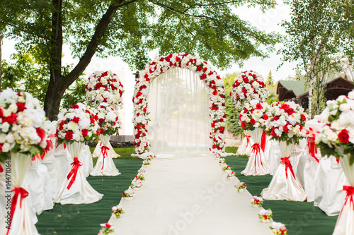 Wedding ceremony outdoors. Wedding arch decorated with red flowers ...