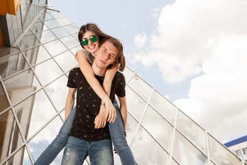 Happy couple posing in fashion style in front of glass office building