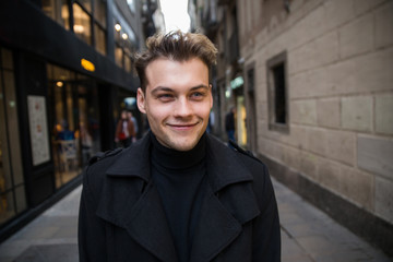 Young happy man in the street with black coat