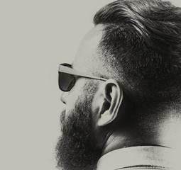 Portrait of a bearded man in sunglasses, with a stylish haircut. Black and white.
