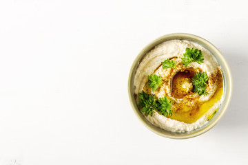 Vegetarian snack. Hummus with greens, dressed with olive oil and paprika in a ceramic plate.