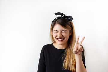 Happy young woman laughing posing with peace gesture. Funny girl wearing trendy headscarf showing tongue grimaces on camera showing victory sign against white wall. Female student having fun indoor
