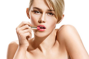 Beautiful young blonde model applying lipstick. Photo of attractive girl with perfect make up on white background. Beauty concept