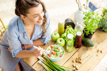 Young and happy woman eating healthy salad sitting on the table with green fresh ingredients indoors Wall mural