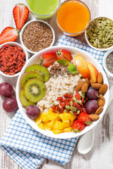 oatmeal porridge with fresh fruit and superfoods for healthy breakfast, vertical top view