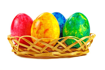 Easter eggs in wicker basket on a white background