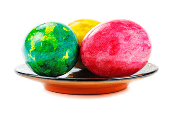Colored Easter eggs in a round dish on a white background