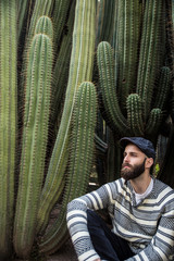 Young man sitting near huge cactus