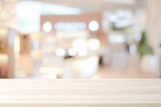 Empty wooden table over blur store background, product and food display montage background