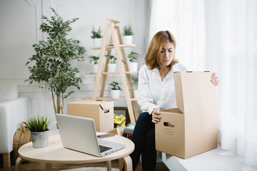 home, post, delivery and happiness concept - young Asia woman opening cardboard box at home