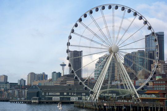 SEATTLE, WASHINGTON, USA - JAN 25th, 2017: A view on Seattle downtown from the waters of Puget Sound. Piers, skyscrapers, Space Needle and Ferris wheel in Seattle city before sunset