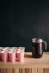 Juice of glass jars with red paper cups against blackboard with space for text.
