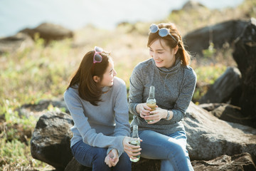 summer, holidays, vacation, happy people concept - smiling Asia girlfriends with bottles of beer or non-alcoholic drinks