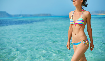 beautiful sexy woman dressed in bikini walking on the beach along the sea front. vacation and travel photography concept