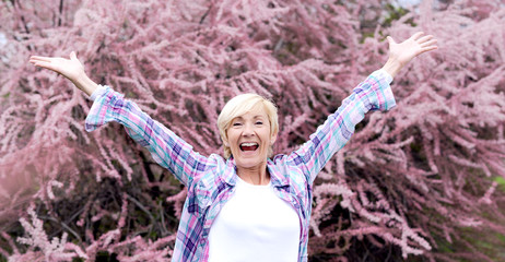 Vibrant blonde middle aged woman Happy and smiling outdoors - seasonal