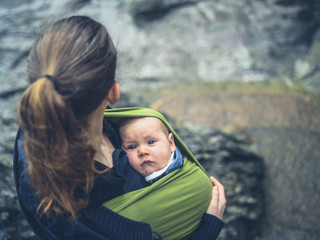 Young mother with baby in sling outdoors