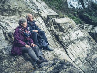 Senior couple sitting on rocks