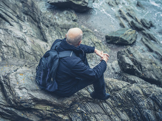 Senior man sitting on rocks