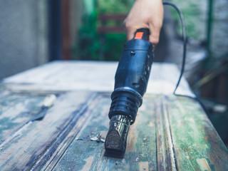 Man stripping paint with heat gun