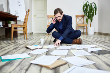 Portrait of middle aged bearded man speaking by phone and sorting documents sitting on floor in office
