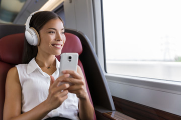 Woman on train listening to music on smartphone. People lifestyle. Young urban businesswoman using phone app, wireless headphones to listen to audiobook. Asian girl enjoying travel in business class.