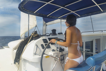 Beautiful brunette woman in white swimsuit is standing a back on the deck of yacht and controlling steering wheel olling a steering wheel