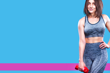 Sport fitness woman doing exercise with red dumbbells near a blue wall. Copy space for advertisement poster.