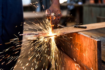 Worker cutting metal sheet by acetylene torch with bright sparks in fabication factory.