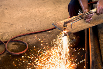 Worker cutting metal sheet by acetylene torch with bright sparks in fabrication factory.