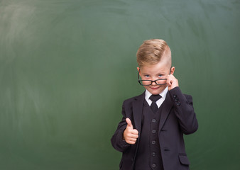 Boy in a business suit showing thumbs up near empty green chalkboard