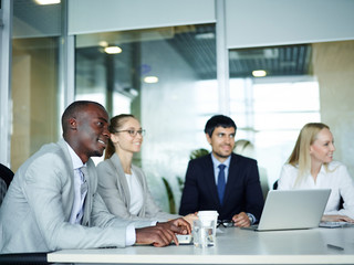 International group of young enthusiastic business people smiling sitting round meeting table in conference room of modern office