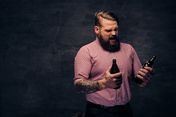 A bearded fat male holds a beer bottle.