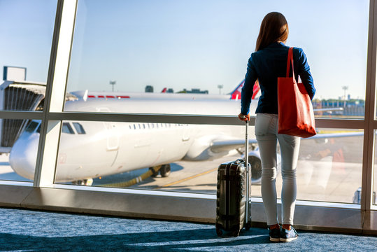 Travel tourist standing with luggages watching sunset at airport window. Unrecognizable woman looking at lounge looking at airplanes while waiting at boarding gate before departure. Travel lifestyle.