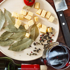 Wine and various snacks, traditional Italian food. Cheese, cherry tomatoes, rosemary, spices. View from above. Closeup.
