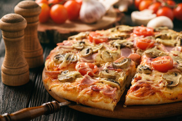 Homemade pizza with ham,mushrooms, tomatoes and cheese.