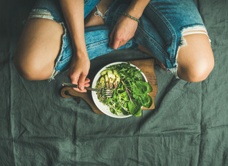 Green vegan breakfast meal in bowl with spinach, arugula, avocado, seeds and sprouts. Girl in jeans...